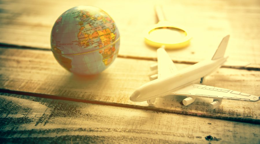 Mini airplane and Globe and Magnify Glasses on wooden table texture background. World map travel and Vacation around the world concept